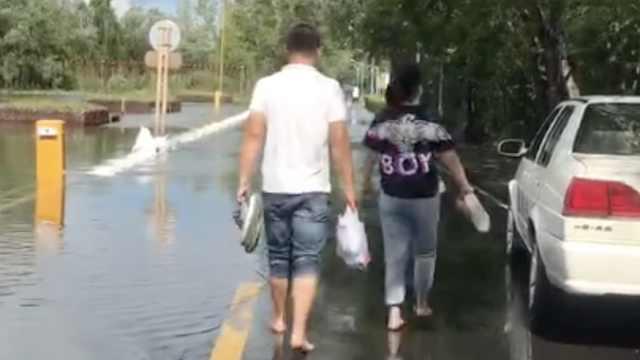 受台风影响镜泊湖超出最高水位15厘米,游客拎鞋水中行走
