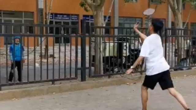 大学生隔栅栏与外卖小哥打羽毛球:刚买的球拍试质量