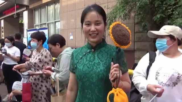 旗袍妈妈手举向日葵和橘子送儿子高考:寓意一举夺魁