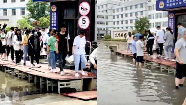 暴雨致中考考点被淹,这个校长带队水中用课桌搭建爱心桥
