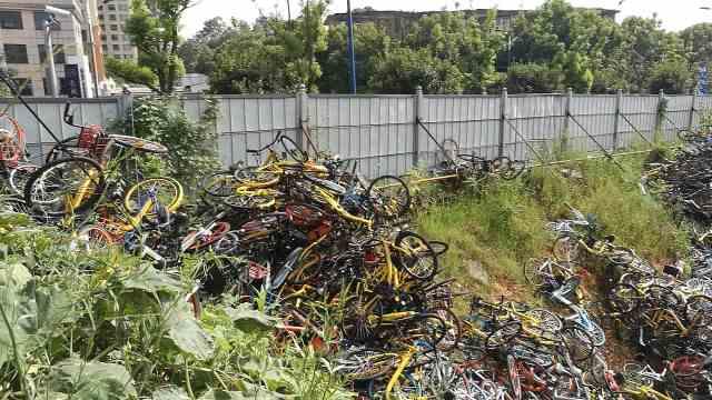 上千辆共享单车被弃,堆积成
