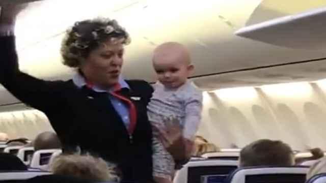 空姐边工作边哄娃,孩子向乘客飞吻